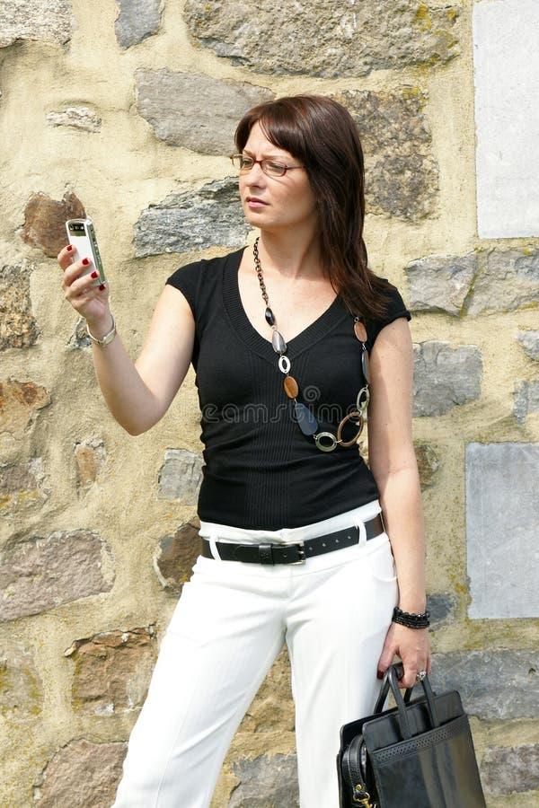 Geschäftsfrauporträt draußen mit Telefon stockfotografie