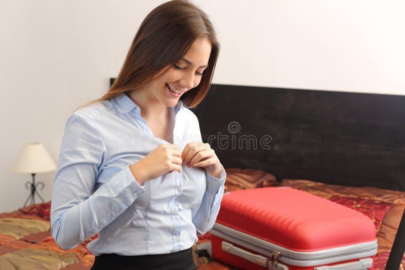 Geschäftsfraureisender, der in einem Hotelzimmer sich auszieht stockbild