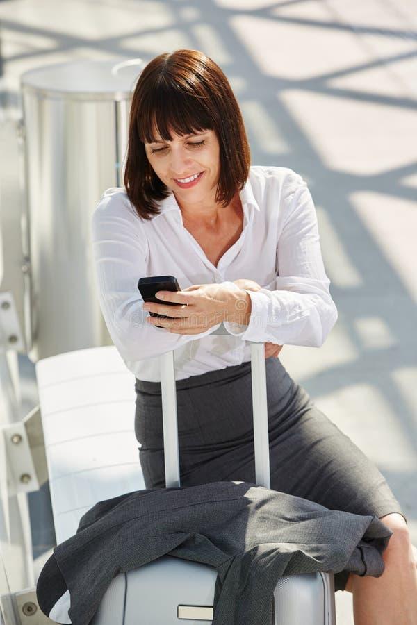 Geschäftsfraureisender, der mit Telefon und Koffer wartet stockbild