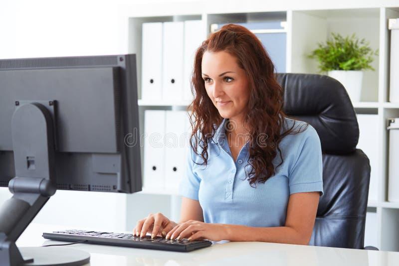 Geschäftsfrauschreiben auf einem Computer stockfotografie
