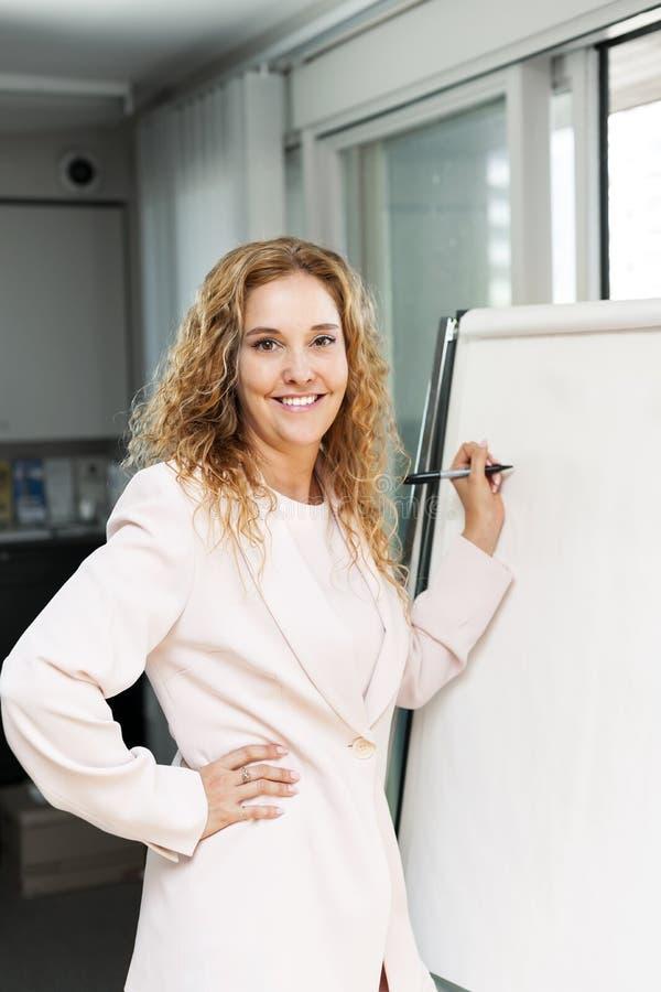 Geschäftsfrauschreiben auf Flip-Chart lizenzfreie stockfotografie
