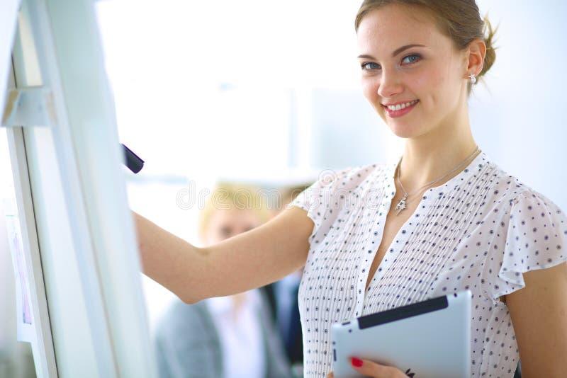 Geschäftsfrauschreiben auf flipchart beim Geben den Kollegen im Büro von Darstellung lizenzfreies stockfoto