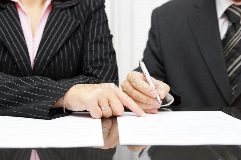 Geschäftsfraushow ein Geschäftsmann, zum einer Vereinbarung zu unterzeichnen lizenzfreie stockfotos