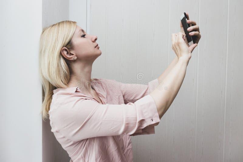 Geschäftsfraustellung nahe der Wand und dem Herstellung selfie lizenzfreies stockfoto