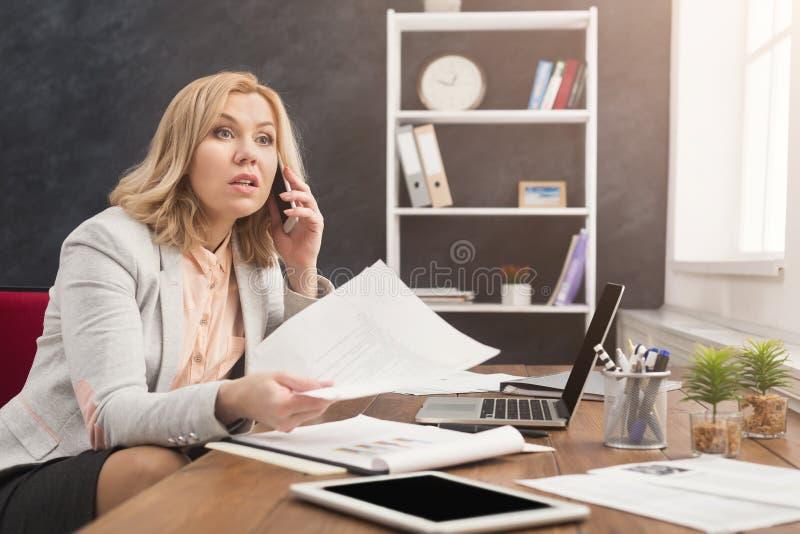 Geschäftsgespräch, ernste Frau, die sich telefonisch im Büro berät stockfotografie