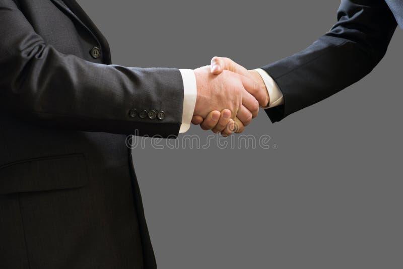 Geschäftshändedruck von zwei Geschäftsmännern in den Klagen lokalisiert auf grauem Hintergrund lizenzfreies stockbild