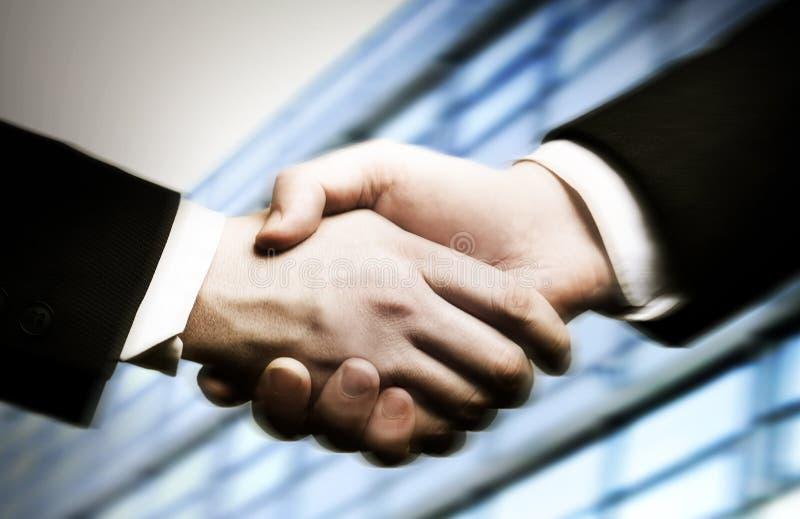 Geschäftshanderschütterung und ein Büro im Hintergrund lizenzfreies stockfoto