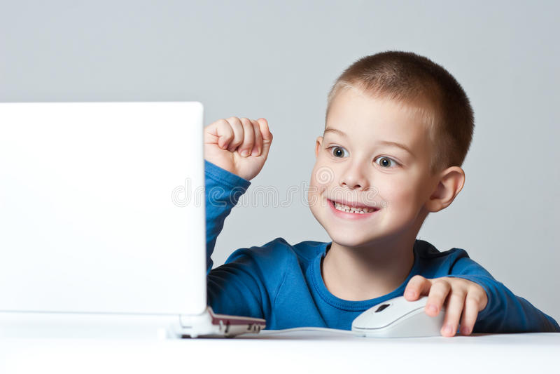 Geschäftsjungenlächeln, das unter Verwendung des Laptops arbeitet lizenzfreie stockfotografie