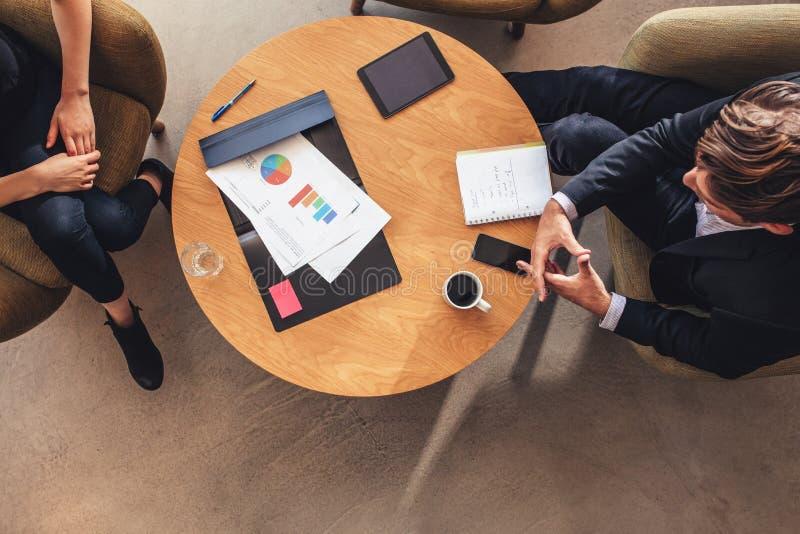Geschäftskollege, der bei Tisch während der Hauptversammlung sitzt lizenzfreie stockbilder
