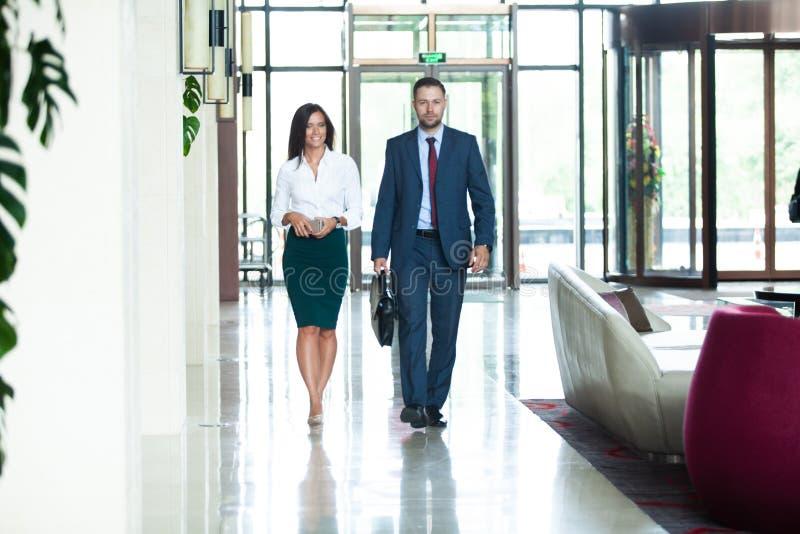 Geschäftskollegen, die auf einander beim Gehen in den Korridor im Büro einwirken lizenzfreies stockbild