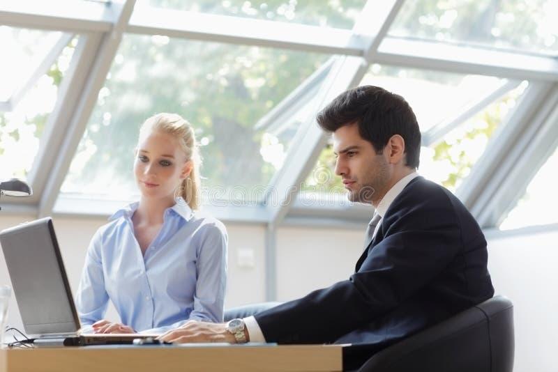 Geschäftskollegen, die an einem Laptop arbeiten stockbild
