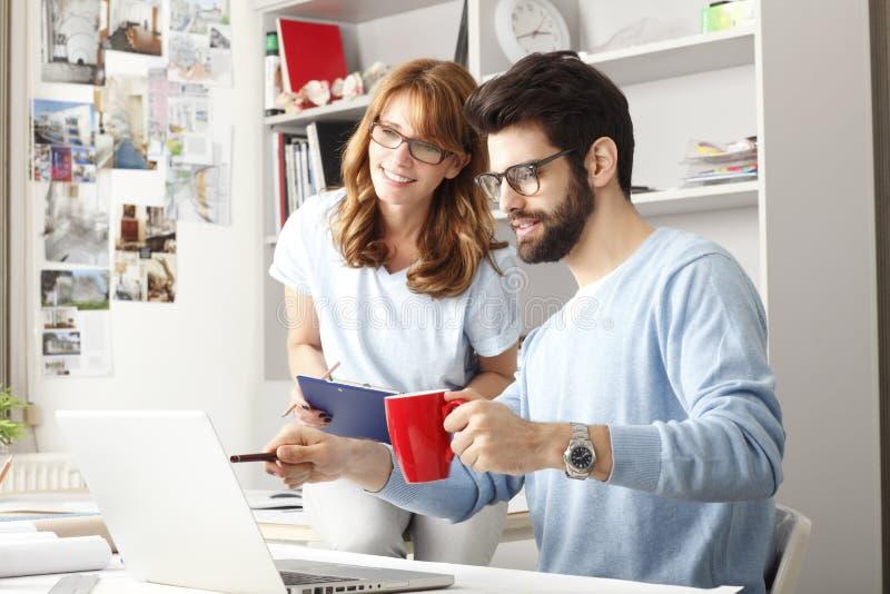 Geschäftskollegen, die an einem Laptop arbeiten stockbilder