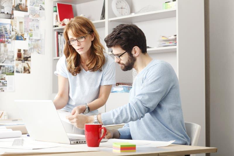 Geschäftskollegen, die an einem Laptop arbeiten lizenzfreie stockfotos