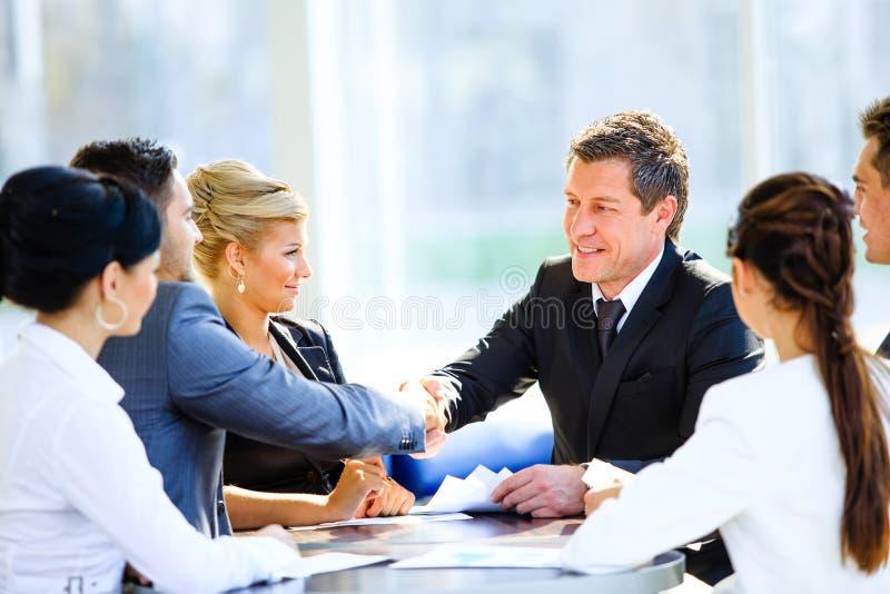 Geschäftskollegen, die an einem Tisch während sitzen stockbild