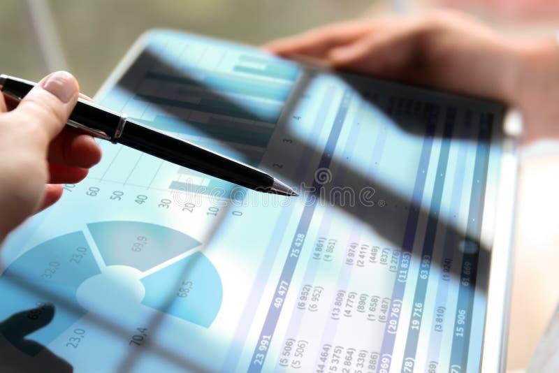 Geschäftskollegen, die Finanzzahlen auf Diagramme bearbeiten und analysieren stockbild
