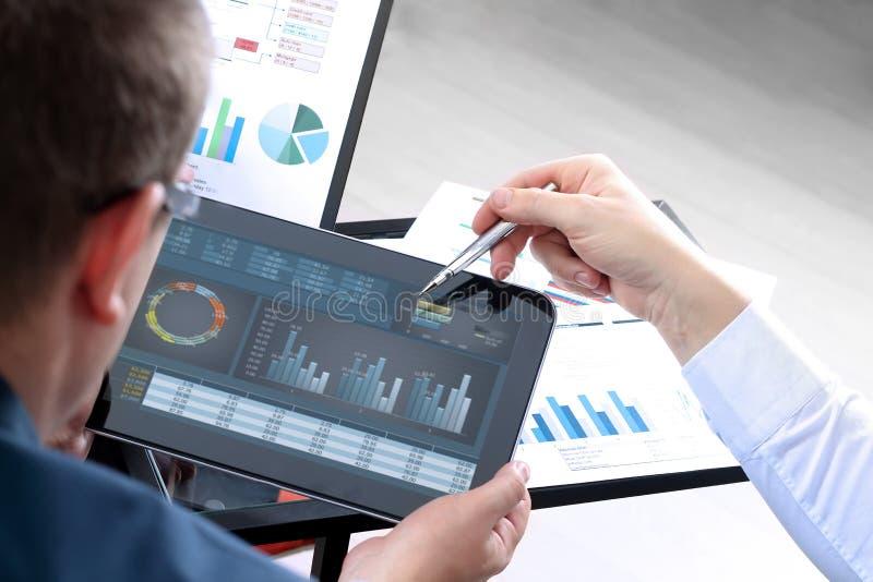 Geschäftskollegen, die Finanzzahlen auf Diagramme bearbeiten und analysieren stockfoto