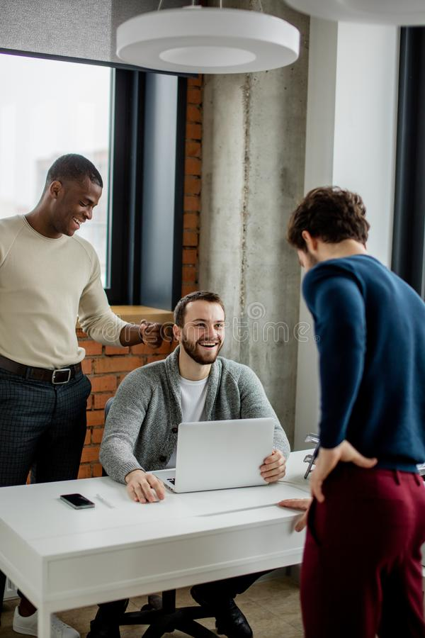 Geschäftskollegen, die Gespräch haben und Laptop im Büro nahe Fenster verwenden stockbilder