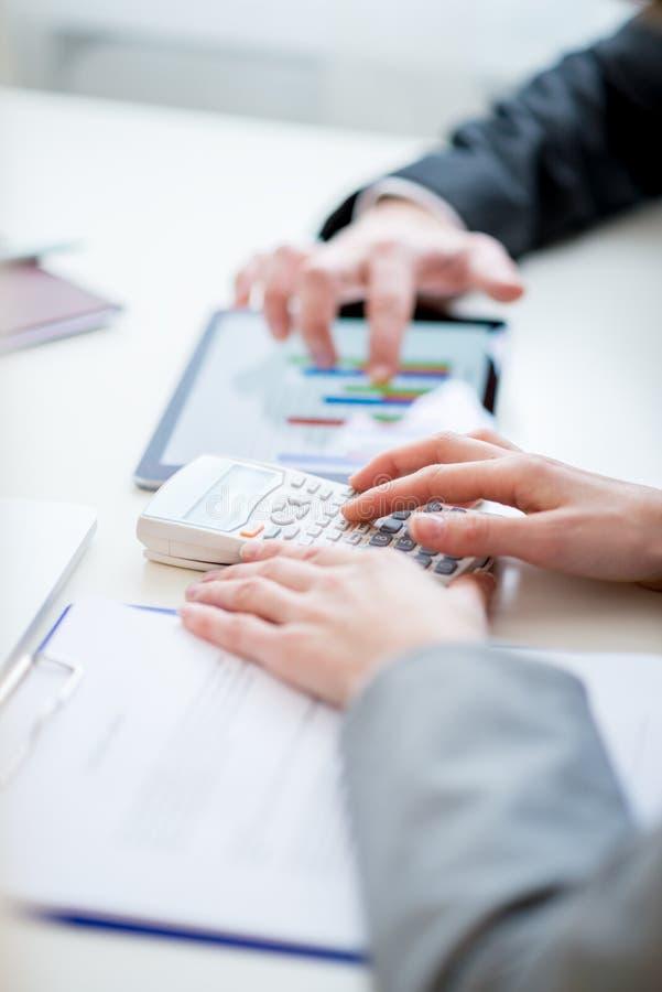 Geschäftskollegen, die Wirtschaftsstatistik vergleichen lizenzfreie stockfotografie