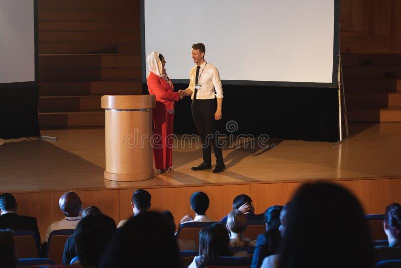 Geschäftskollegestellung und Diskussion mit einander vor dem Publikum im Auditorium lizenzfreie stockbilder