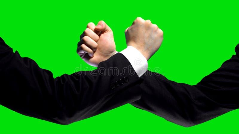 Geschäftskonfrontation, Fäuste auf grünem Schirmhintergrund, Wettbewerbsmarkt stockfotos