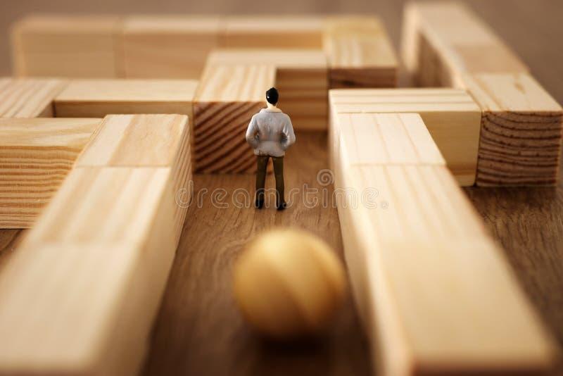Geschäftskonzept Bild der Herausforderung Ein Mann steht im Labyrinth, das nach dem Ausgang und ahnungslos von der Gefahr sucht,  stockbild