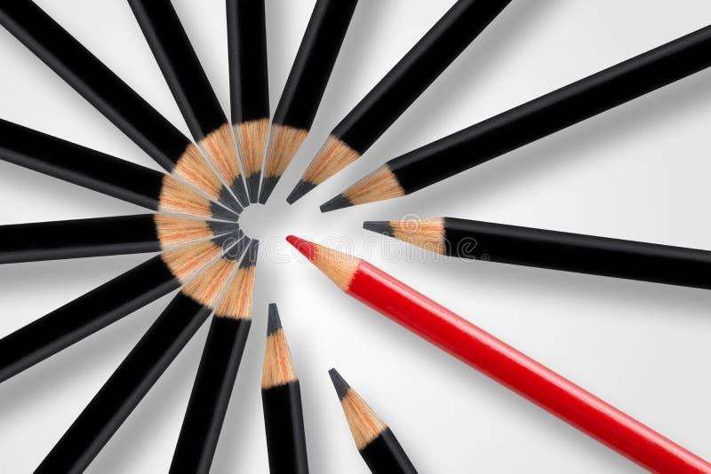 Geschäftskonzept der Unterbrechung, Führung oder diiferent denken; roter Bleistift, der auseinander Kreis von schwarzen Bleistift stockfotografie