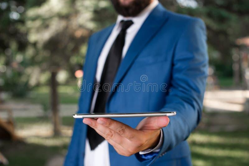 Geschäftskonzept mit Mannholdinghandy mit Touch Screen Geschäftsmann hält Schossspitze in seiner Hand Gesch?ftsmann herein stockbilder