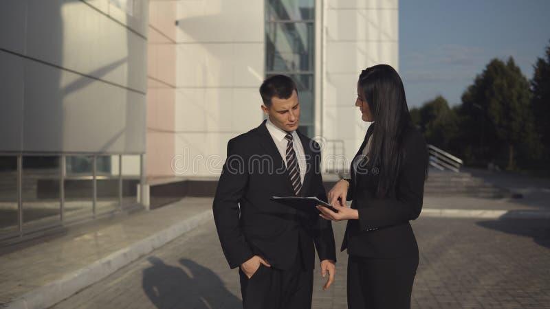Geschäftsleute beim Arbeiten nahe Bürogebäude lizenzfreie stockfotografie