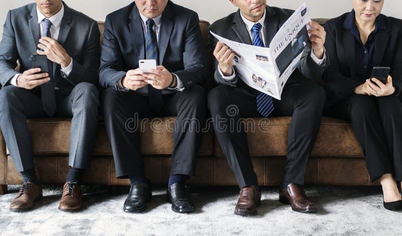Geschäftsleute beschäftigt mit Mobile- und Lesezeitung stockfoto
