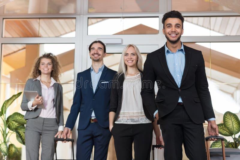 Geschäftsleute in der Hotel-Lobby, Mischungs-Rennwirtschaftler-Gruppen-Gäste kommen an lizenzfreie stockfotos