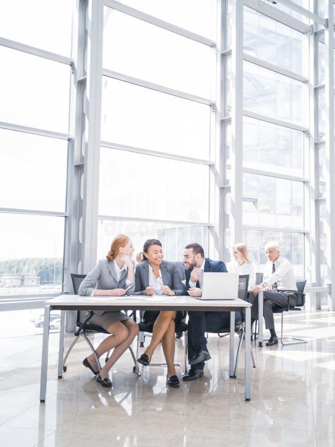 Geschäftsleute, die über Arbeitsplatz lachen stockfotografie
