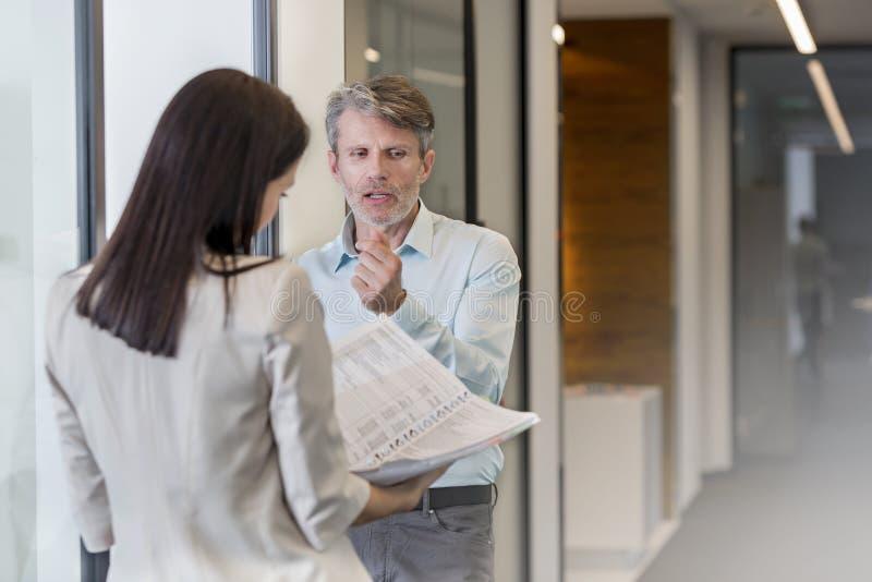 Geschäftsleute, die über Datei am Bürokorridor sich besprechen lizenzfreies stockfoto