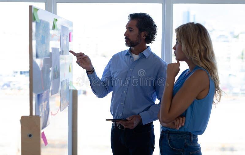 Geschäftsleute, die über Diagramm auf Glaswand in einem modernen Büro sich besprechen stockbild