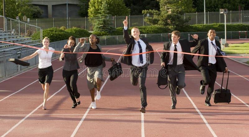 Geschäftsleute, die über die Ziellinie laufen lizenzfreie stockfotografie