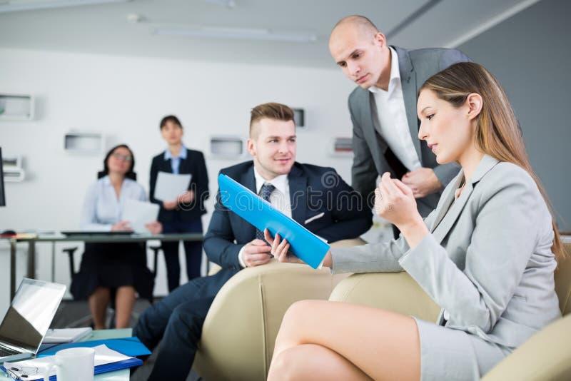 Geschäftsleute, die über Klemmbrett im Büro sich besprechen stockbild