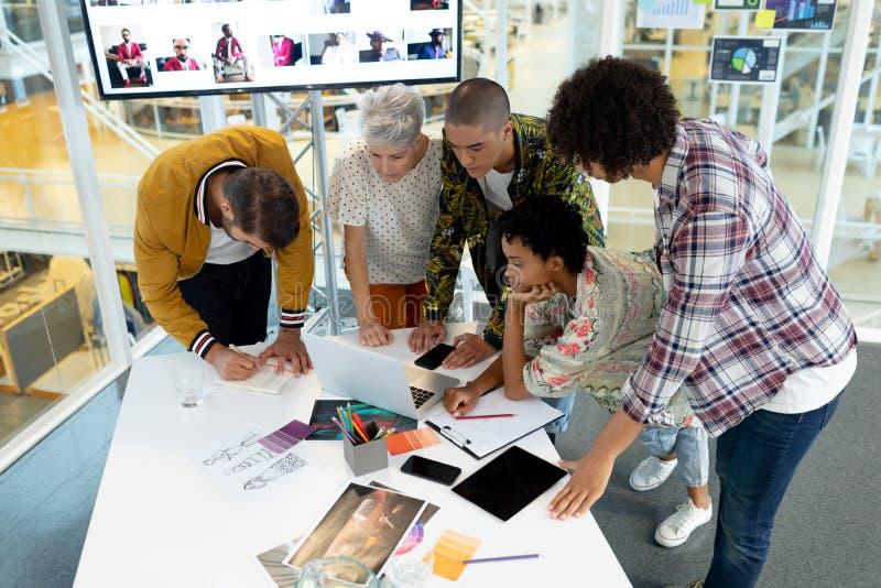 Geschäftsleute, die über Laptop im Konferenzsaal sich besprechen stockfotografie