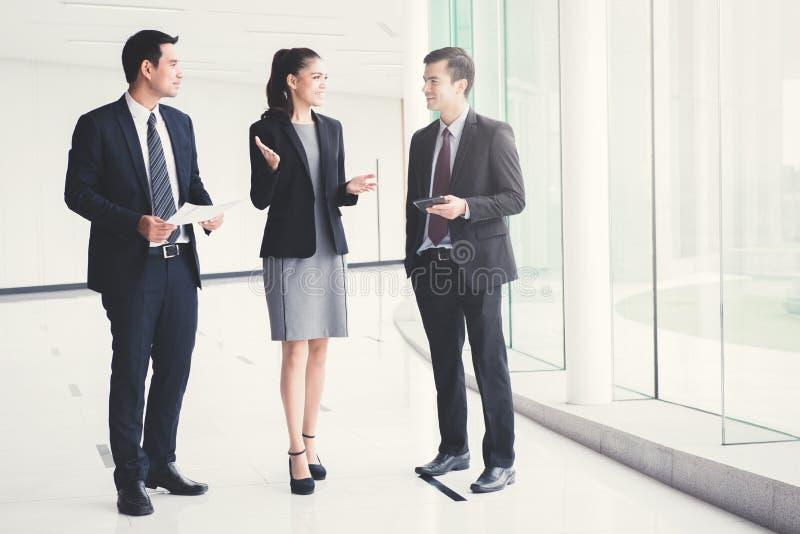 Geschäftsleute, die Arbeit in der Gebäudehalle sprechen und besprechen stockfotos