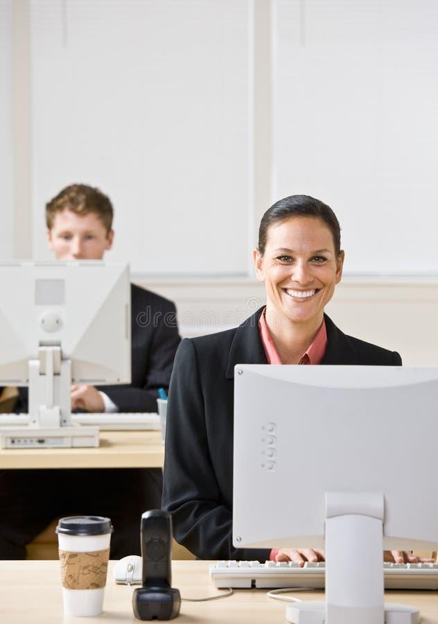 Geschäftsleute, die auf Computern schreiben lizenzfreie stockfotos