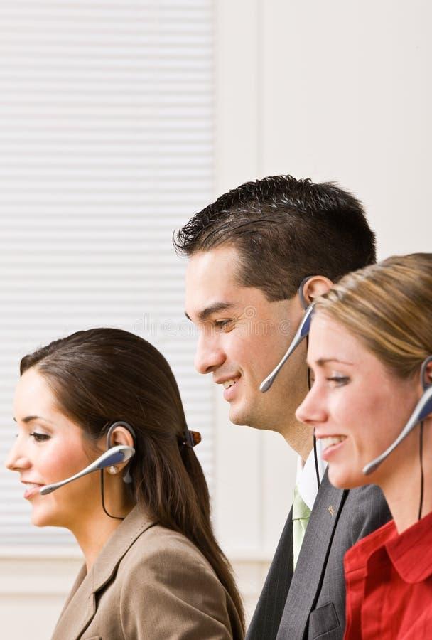 Geschäftsleute, die auf Kopfhörern sprechen lizenzfreie stockfotos