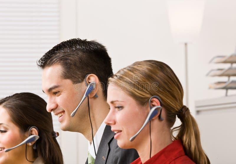 Geschäftsleute, die auf Kopfhörern sprechen stockbild