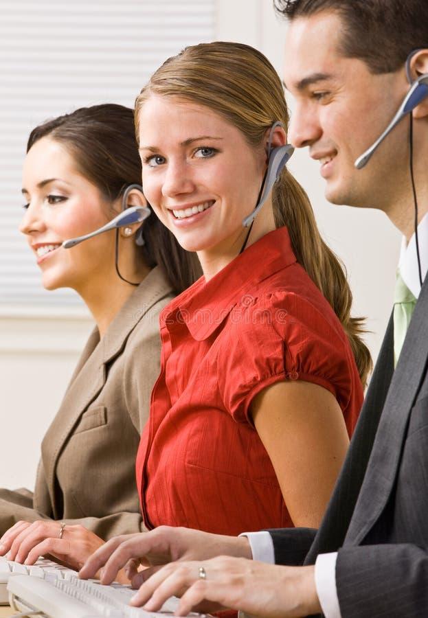 Geschäftsleute, die auf Kopfhörern sprechen lizenzfreies stockfoto