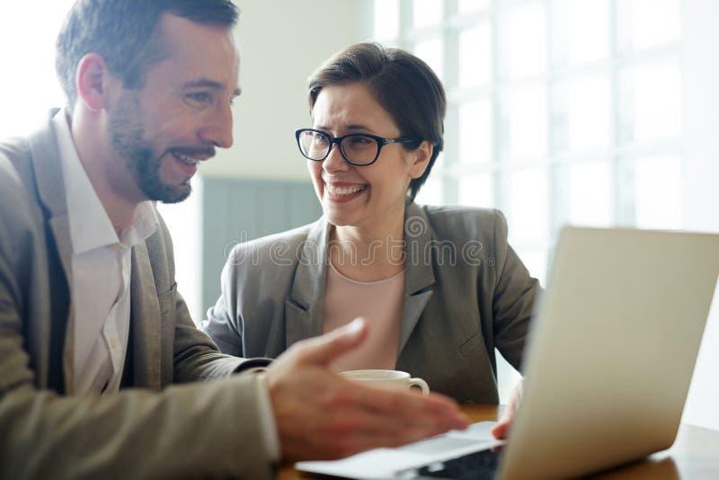 Geschäftsleute, die bei der Arbeits-Sitzung lachen stockfotografie