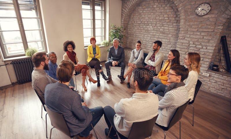 Geschäftsleute, die bei der Gruppensitzung sprechen lizenzfreie stockbilder