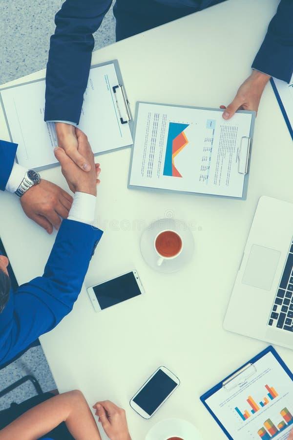 Geschäftsleute, die bei der Sitzung, im Büro sitzen und sich besprechen lizenzfreie stockfotos