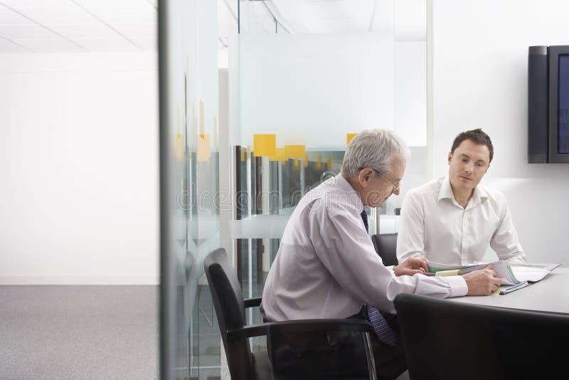 Geschäftsleute, die bei Tisch Dokumente wiederholen stockfotografie