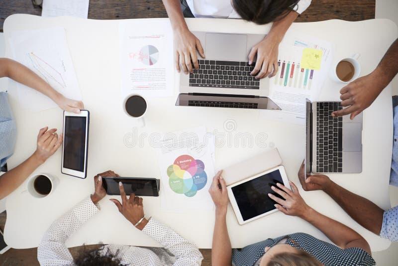 Geschäftsleute, die Computer an einem Schreibtisch, obenliegender Schuss verwenden stockbilder