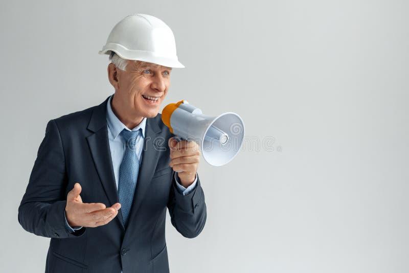 Geschäftsleute, die an dem harten Job arbeiten Erbauer in der Schutzhelmstellung lokalisiert auf dem grauen Sprechen am Megaphon  stockfotos