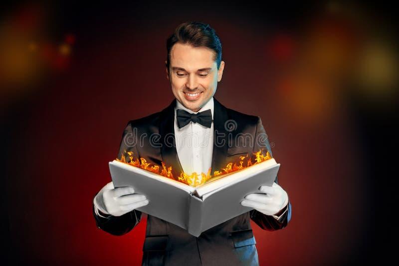 Geschäftsleute, die an dem harten Job arbeiten Magier in der Klage und Handschuhe, die auf Wandlesedem magischen Buchlächeln nett lizenzfreie stockfotos
