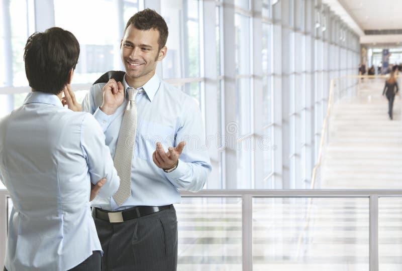 Geschäftsleute, die in der Bürolobby sprechen stockfoto