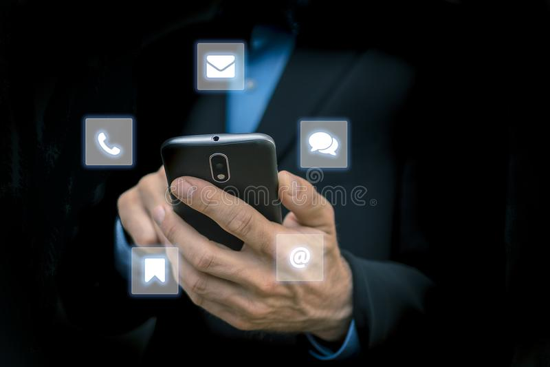 Geschäftsleute, die in der Hand mobilen Smartphone - umgeben durch Netz- und Chatinternet-Zeichen und -symbole halten stockfotos